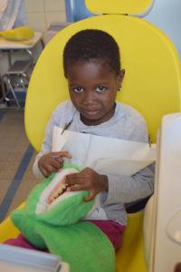 Juwany est assise sur un fauteuil jaune et joue avec une peluche de crocodile.