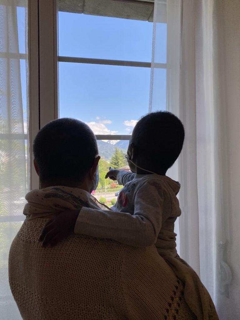 Convoyages d'enfants. Dans les bras de Marie, convoyeuse bénévole, Ibrahima patiente en salle d'attente